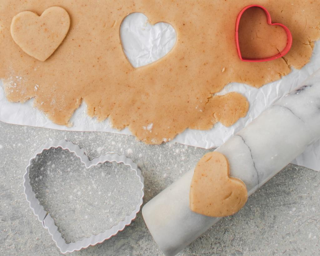 Brown butter sugar cookie dough rolled out on a floured surface.  With cookie cutters and rolling pin.