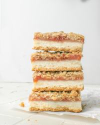 Four plum crumble bars stacked on top of each other, showing layers of shortbread, plum jam, and streusel crumble