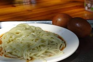 A plate of noodles in peanute and sesame sauce with two tea eggs
