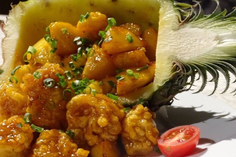 Sweet and sour chicken and potatoes served in half a pineapple