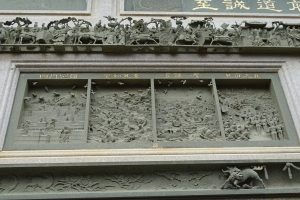 Bas-relief with four panels, soldiers and fighter planes inside, men on horses from an earlier era on top