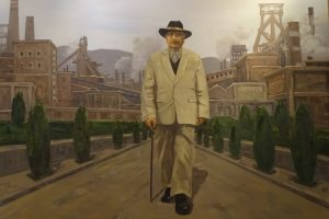 Tan Kah Kee in White Suit walking through street, coal smoking from factory chimneys in distance