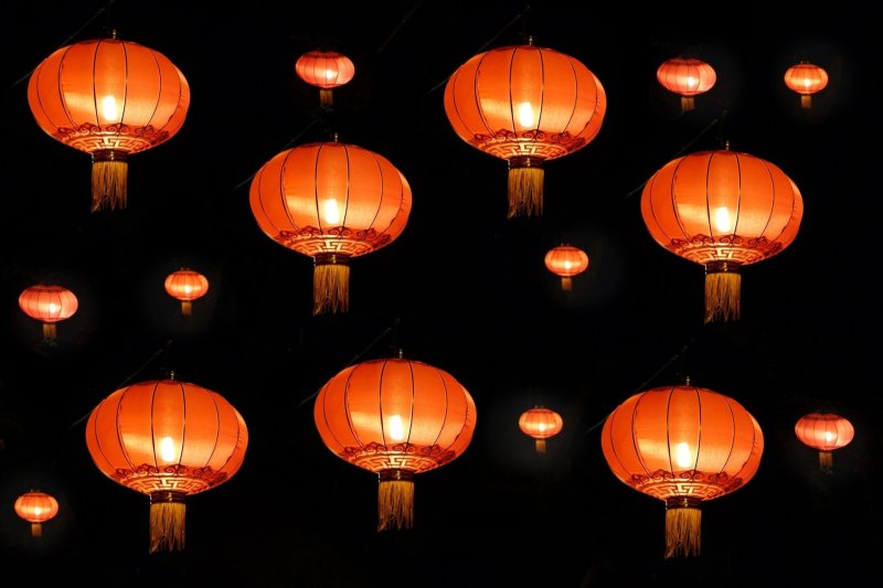 Red Chinese lanterns floating against a black background