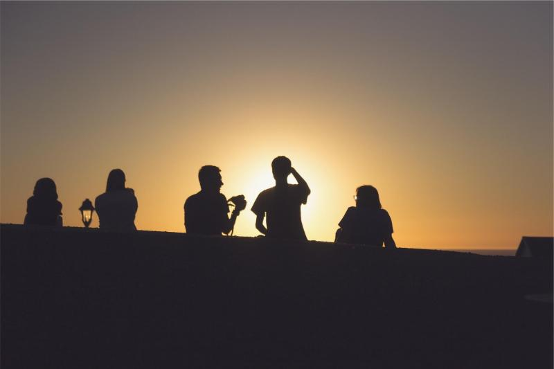 A group of friends with sunset in the background.