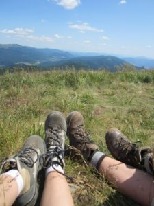 Two pair of legs in hiking boots and mountains in the background.