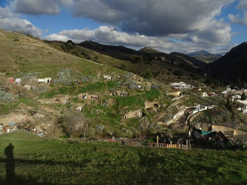 View of Sacromonte village from distance. On the left are the cave dwellings leading into the hills. On the right, you can see the more built up area, with whitewashed houses.