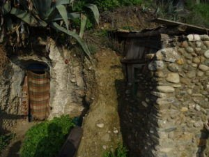 Sacromonte cave dwelling from outside with a cloth over the entrance and a stone wall on the right