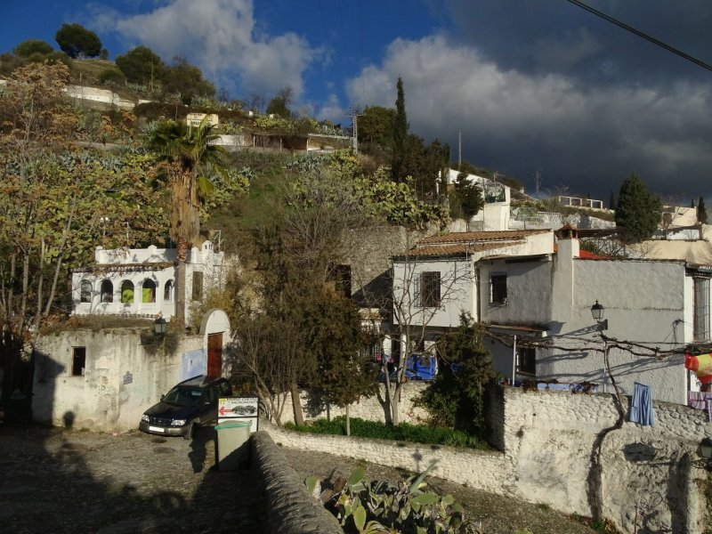 Whitewashed cave houses of Sacromonte village, with Albaicin hill rising out of it
