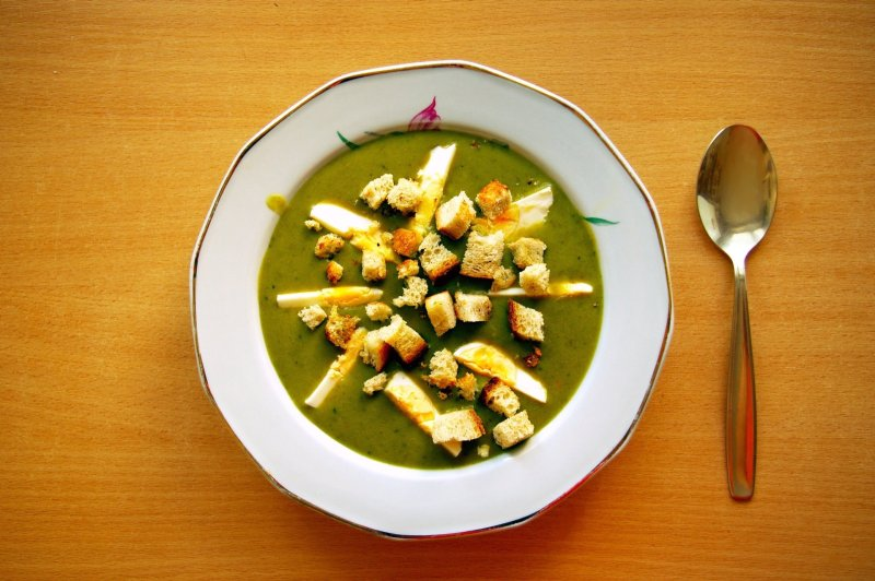 Polish sorrel soup with a bed of croutons and egg floating on top of it