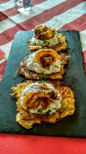 Three potato pancakes with sour cream and salmon on a serving tray