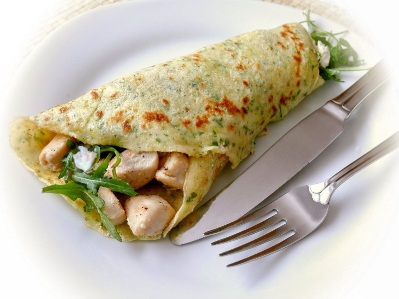 Pancakes with chicken on a plate with cutlery