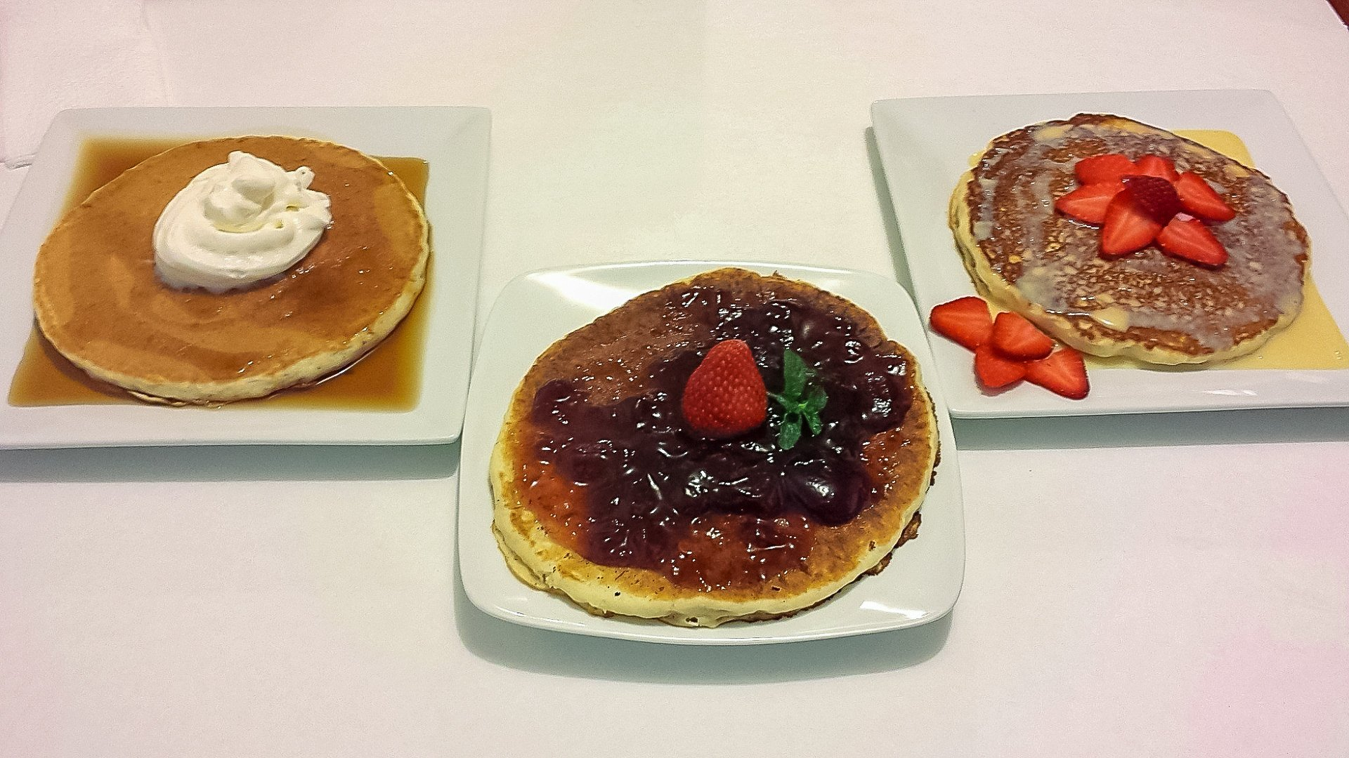 Three plates with pancakes with different toppings