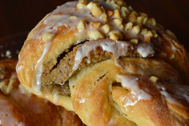 A closeup of a Saint Martin's Croissant with nuts and icing on top.