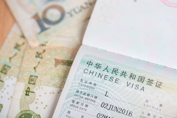 A Chinese L VIsa in a passport with 10 and 1 yuan notes in the background