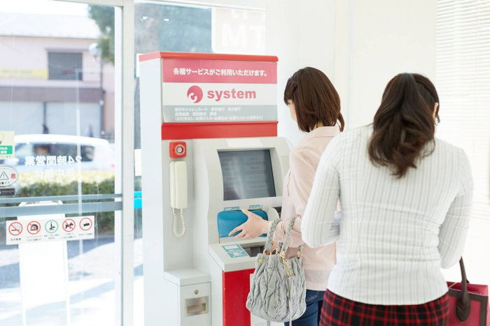 Two women taking out cash from a Chinese cash machine, a glass closed door behind the machine