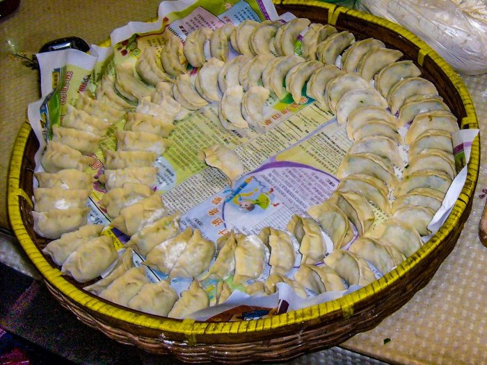 A large bamboo tray of Chinese dumplings, arranged in two concentric circles with a space at the centre.