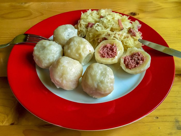 A meal of filled Pyzy with meat inside and some sauerkaut at the top of a red and white plate.