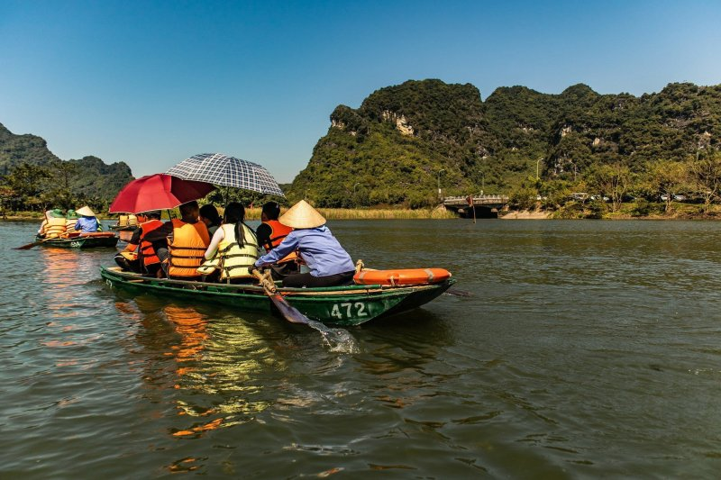 A boat with the number 472 on it on the water. In the foreground we see Vietnamese tourists with parasols and in the background the oarsperson is rowing wearing a Vietnamese conical hat,