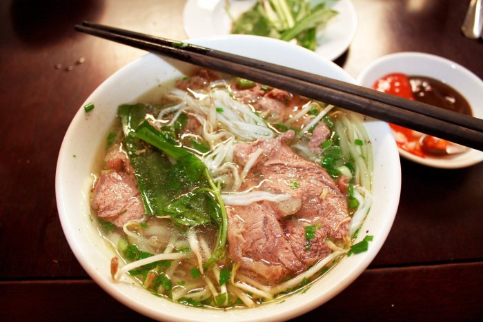A bowl of southern pho with beef, bean sprouts, and a side bowl containing hoisin sauce and chillies.