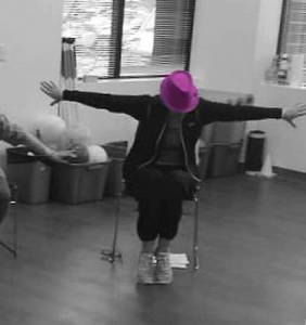 dance class woman in chair pose with purple hat