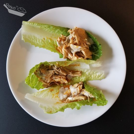 An overhead shot of buffalo chicken dip and ranch dressing in pieces of lettuce as an alternative to tacos and/or chips.