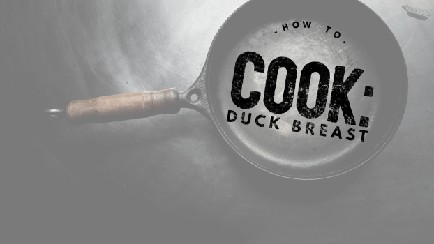 """A lowered opacity image of a cast iron pan with a wooden handle on a black background. Black text inside the pan reads """"How to Cook: Duck Breast"""""""