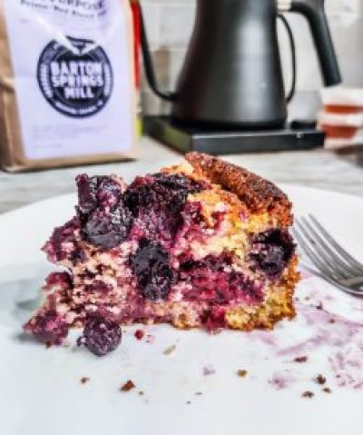 A high contrast image of the blackberry cornmeal cake on a white plate, a few tines of a fork peaking in on the right. In the background you can see the bottom half of my black electric kettle and the label for the Barton Springs Mill flour I used to make the cake.