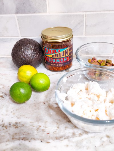Ingredients for this guacamole on a marble countertop. Avocado, key limes, a small clear glass bowl of crumbled feta, a small clear glass bowl of roasted salted pistachios, and a jar of Trader Joe's Chili Onion Crunch.