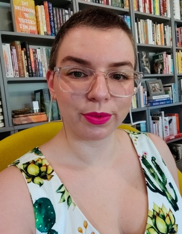 A picture of me with clear glasses and hot pink lipstick in a white dress with cactus print. I am sitting in my favorite yellow chair and behind me is part of my bookshelf.