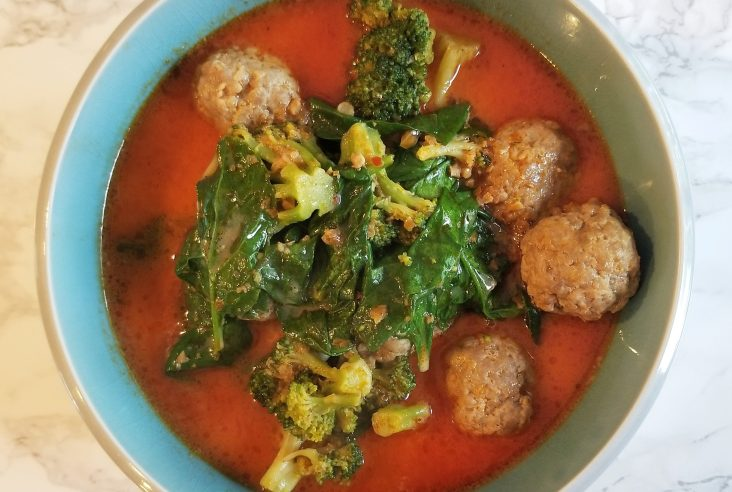 An overhead shot of homemade curry in a blue and gray bowl on a white marble background. In the bowl is red curry with meatballs and sauteed greens.