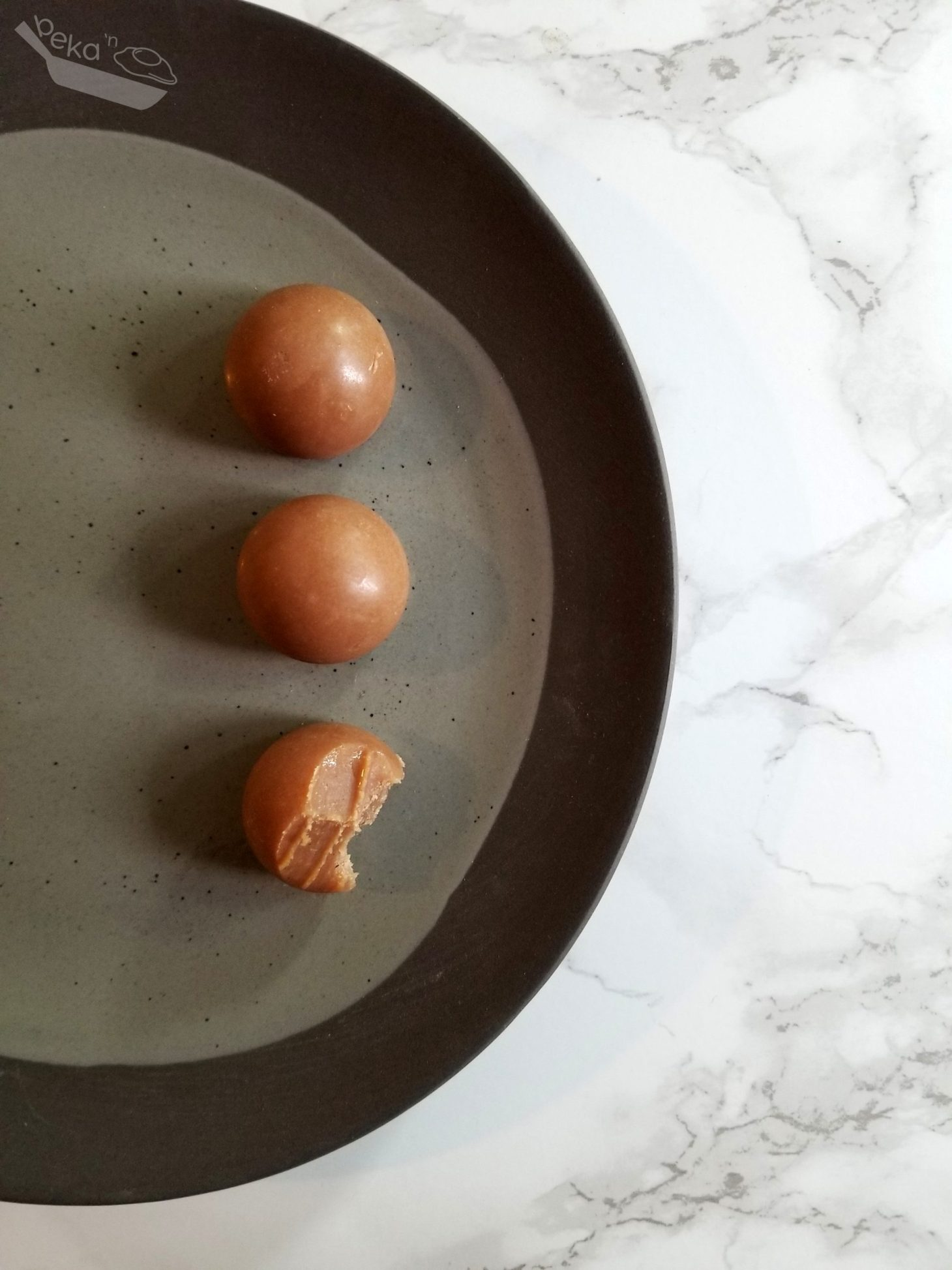 An overhead shot of three salted caramel bites on a gray textured plate on a white marble background. The bottom piece of fudge has a bite taken out of it.