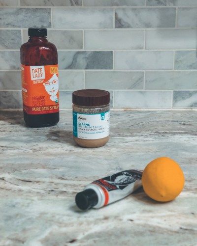 A bottle of date syrup, jar of tahini, tube of harissa paste, and a lemon on my kitchen counter.