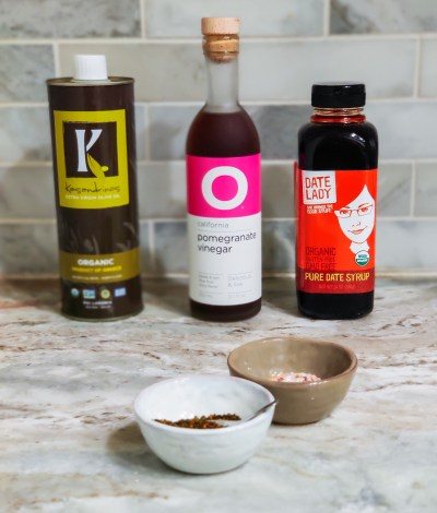 A head-on photograph of Kasandrinos olive oil, O pomegranate vinegar, and Date Lady date syrup on a marble countertop with tile background. In the foreground of the image are two small ceramic pinch bowls - one with zaatar and the other with dried garlic and dried shallots