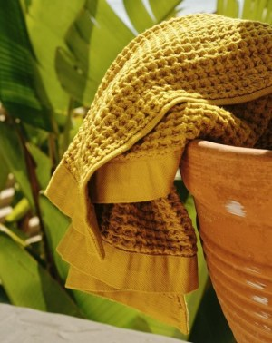 A yellow waffle-knit Onsen towel hanging over the edge of a pot (image from Onsen instagram)