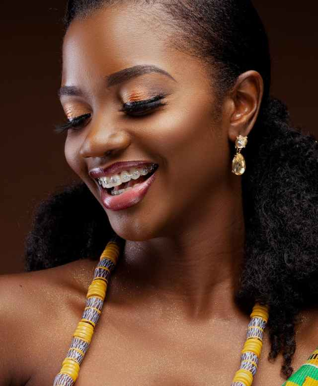 woman wearing yellow and grey beaded accessory