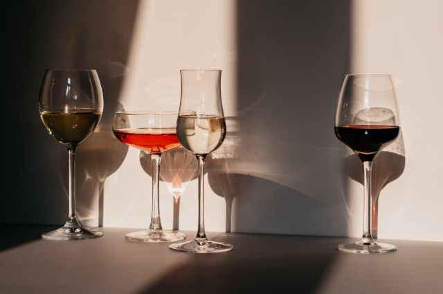 different sorts of wine in various glasses on table in sunlight