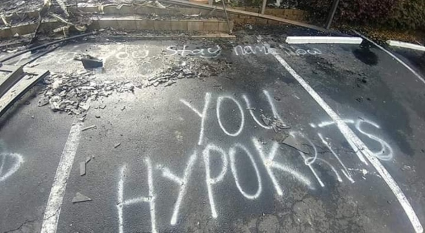 """The graffiti in the parking lot reads: """"Bet you stay home now you hypokrits"""