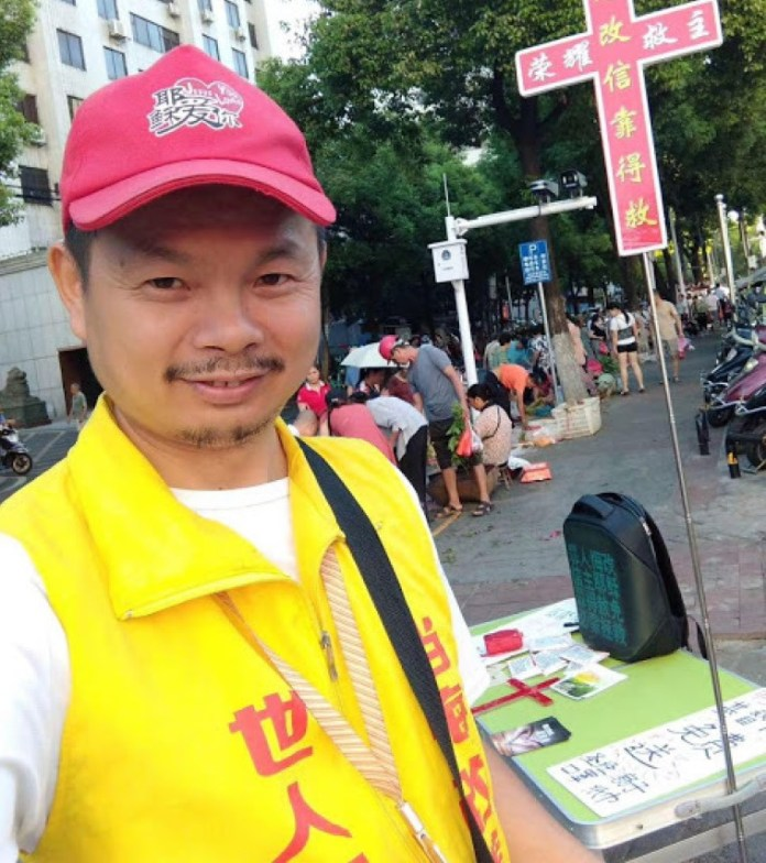 """A street evangelist, Chen often carries a wooden cross inscribed with the words """"Glory to our Savior"""" and """"Repent and Be Saved by Faith"""" as he shares the Gospel with passersby."""