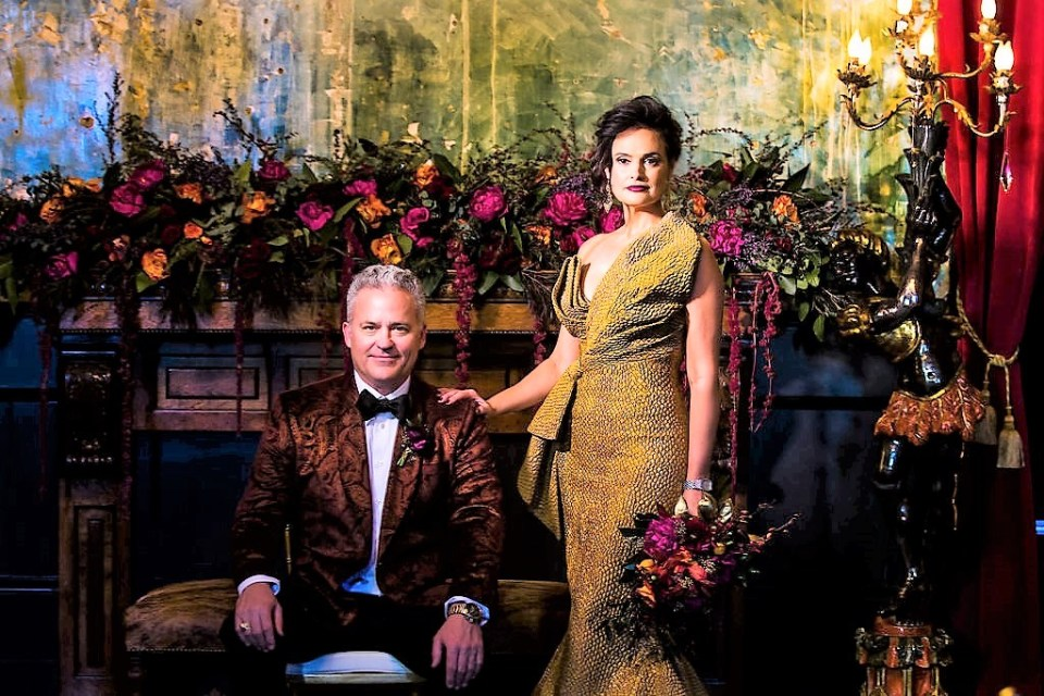 A regal couple pose at their glamorous statement wedding