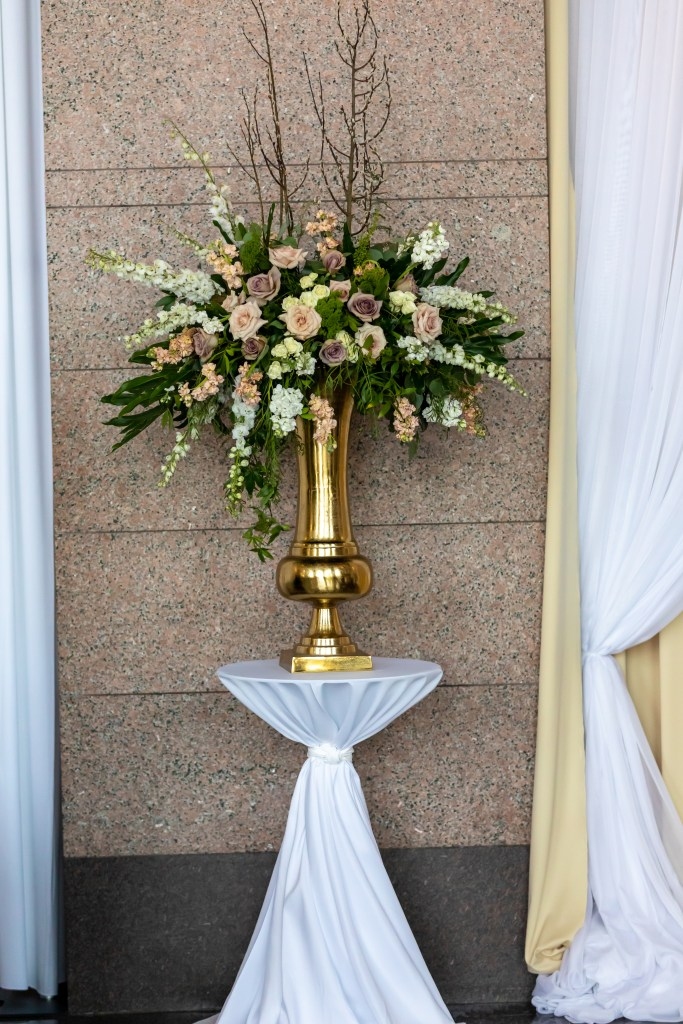 A luxurious blush arrangement topping a stunning gold vase at the entryway!