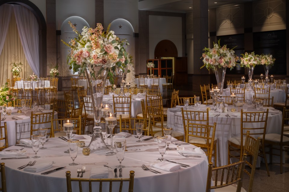 Tall and lavish clear glass vases almost make it seem that these luxurious blush arrangements are floating among the candle-lit tables!