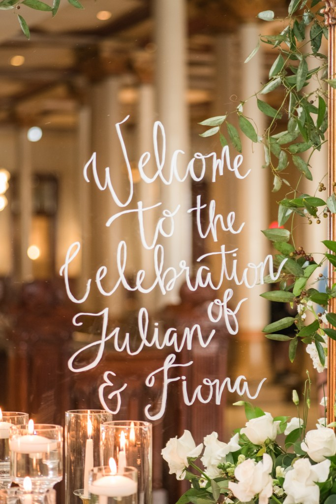 Beautiful greenery and ivory blooms frame the welcome sign for this timeless spring wedding.