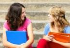 két fiatal lány ül a lépcsőn és beszélgetnek