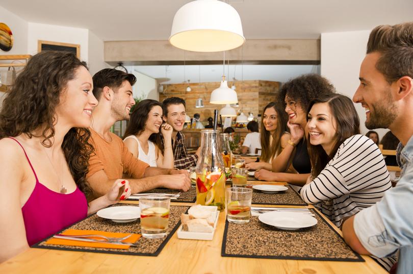 fiatalok ülnek a terített asztal körül