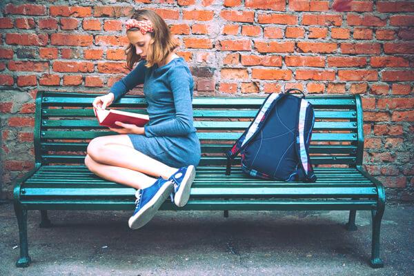 lány ül a padon és könyvet olvas