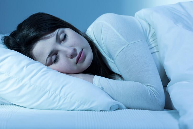 fehér ágyneműben alvó lány