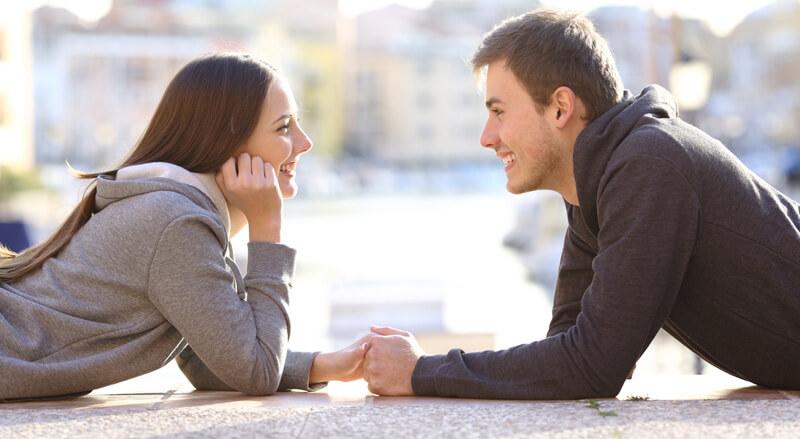 fiatal pár egymással szemben mosolyog