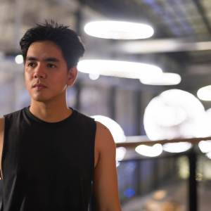 Young handsome Asian man thinking in the city outdoors at night