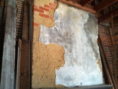 Deteriorating plaster above the fireplace