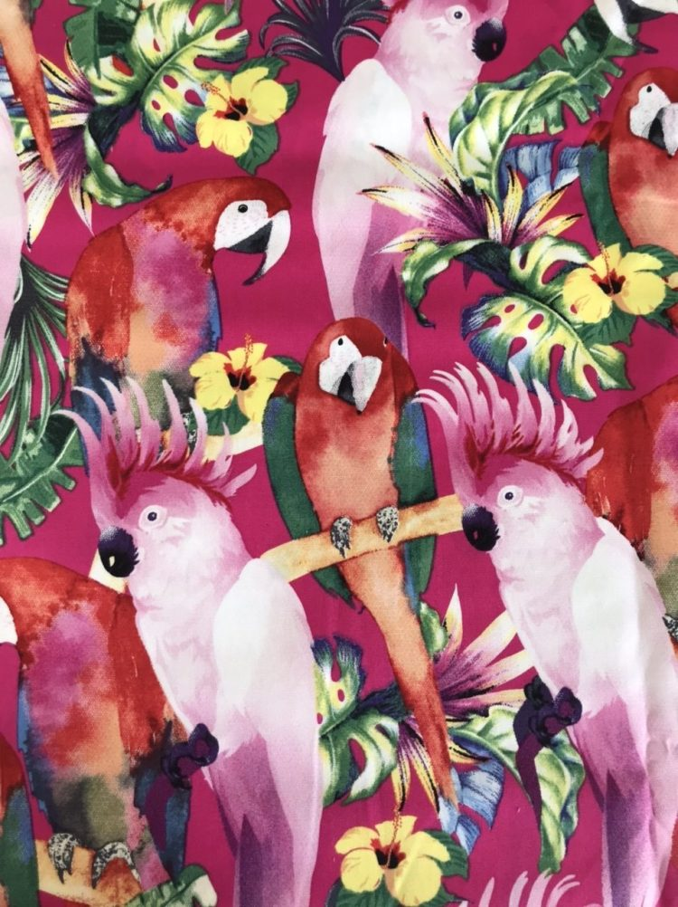 Pink fabric with Tropical Birds including Red Macaw and Cockatoos with Green Monsteria leaves and Yellow Hibiscus flowers